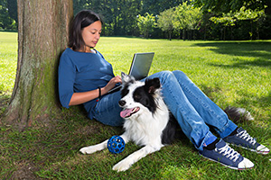 woman with laptop and dog under tree